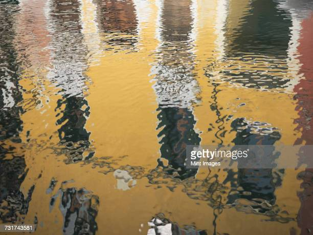 Reflections in the water of colourfully painted house fronts in the city of Venice.