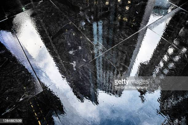 reflections in the wet sidewalk of modern office skyscrapers in the city of london - bank stock pictures, royalty-free photos & images