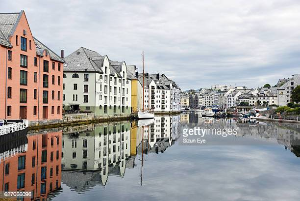 Reflections in water of old historical houses in the old port of Alesund in Norway.