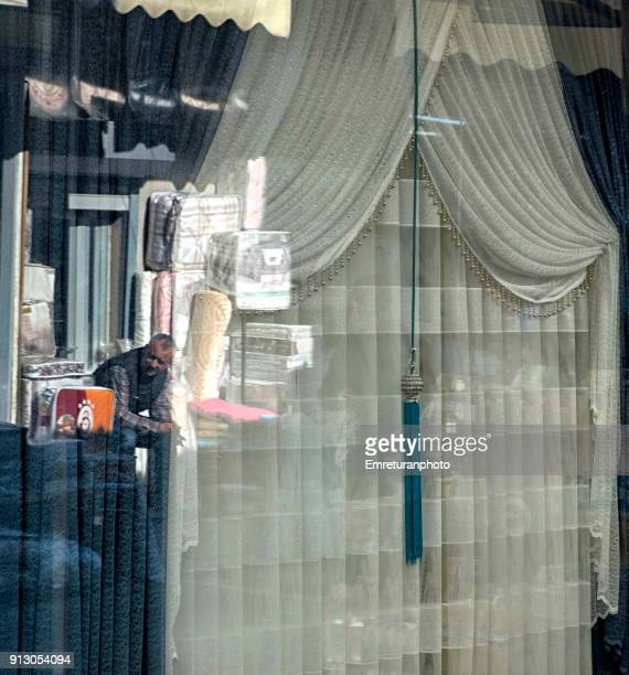 reflections of a salesman on shop window,kemeralti. - emreturanphoto stock pictures, royalty-free photos & images
