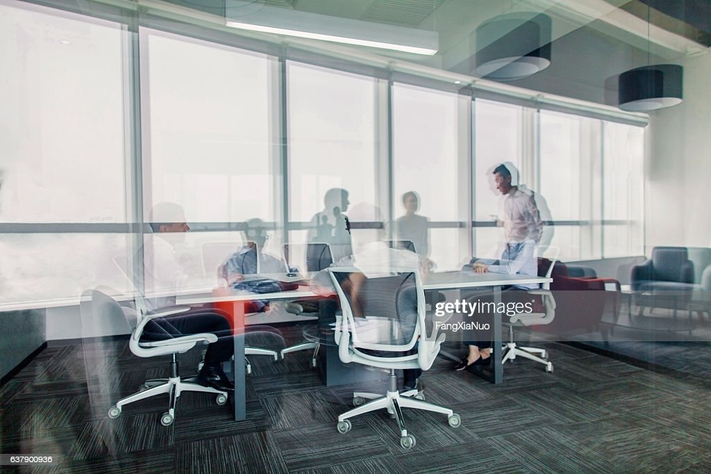 Reflections of business colleagues having meeting in office : Stock Photo