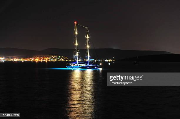 reflections of illuminated sailboat - emreturanphoto stock pictures, royalty-free photos & images