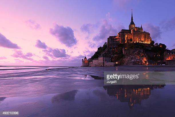 reflections of mont saint-michel lit in the evening - unesco world heritage site stock pictures, royalty-free photos & images