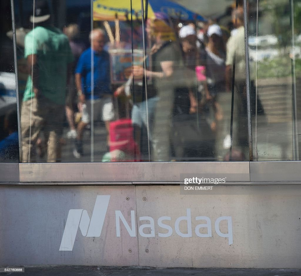 Reflections of people are seen in the windows of the Nasdaq offices in Times Square on June 24, 2016 in New York. US stocks tumbled early Friday, with banking equities suffering especially deep losses, joining an international rout after Britain's surprise vote to exit the European Union. The Dow sank more than 500 points shortly after the markets opened at 1330 GMT, but then quickly recovered some of the losses. The selloffs in the US were smaller than in many overseas markets. EMMERT