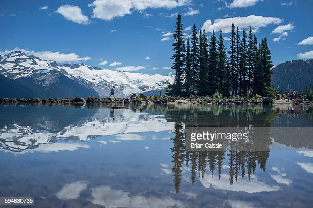 reflections of trees and snow covered mountain on garibaldi lake - garibaldi park stock pictures, royalty-free photos & images