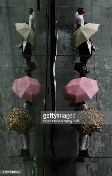 Reflections on the glass panels of Landmark show pedestrians crossing the road in Central district under the rain when standby signal number one is...