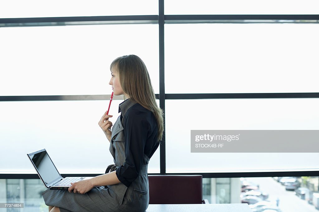 Reflective businesswoman cross-legged on table while using a laptop : Photo