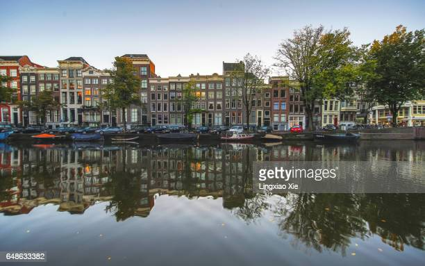 Reflective cityscape of Amsterdam canal before sunrise, Netherlands