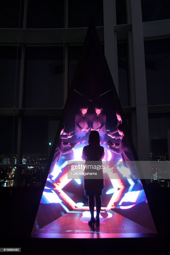Reflective echo by WOW is displayed at the Media Ambition Tokyo at Roppongi Hills on February 8, 2018 in Tokyo, Japan. Artwork details. This work repeatedly reflects a kaleidoscopic animation by projecting an image onto the base of a mirror coated pyramid. The image, spreading out as though to infinity, welcomes visitors by creating a space that blends truth and falsehood, appearing at times like a flower and at others like a geometric figure.