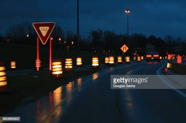 reflective neon construction barrels along the highway - detour sign stock photos and pictures