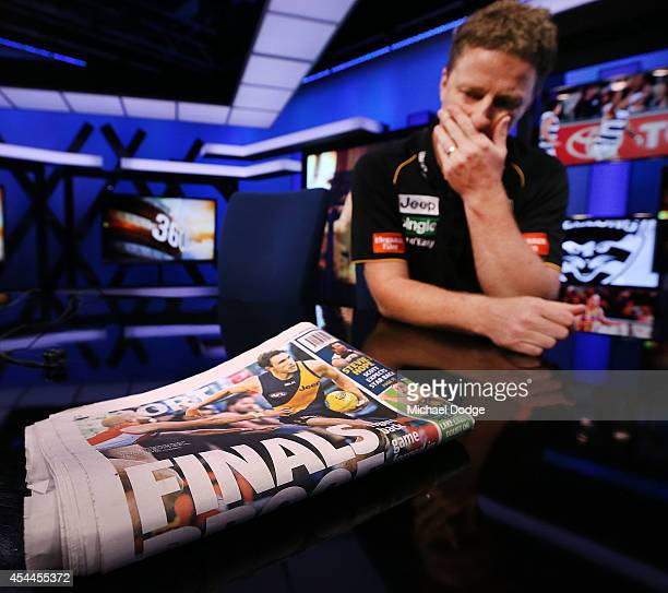 A reflective Tigers coach Damien Hardwick looks at the paper before speaking to the media during the AFL Finals Series Launch at Fox Footy on...
