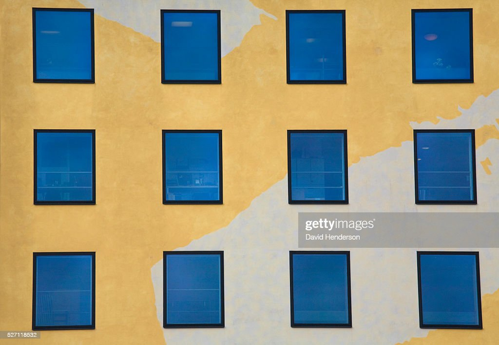 Reflective windows in a yellow building : Stockfoto