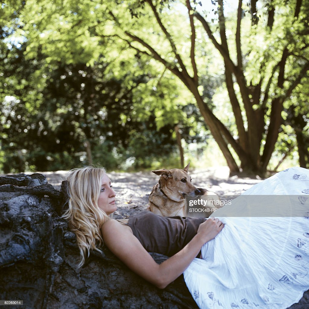 Reflective young woman leaning against trunk, dog beside of her : Stock Photo