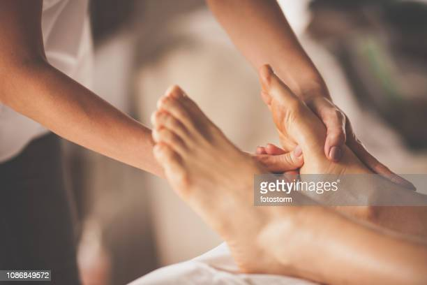 reflexologist applying pressure to foot with thumbs - massage stock pictures, royalty-free photos & images