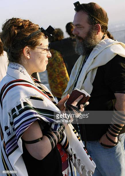 A Reform Jewish woman wearing phylacteries and prayer shawl customarily wore only by men prays on the roof of Tel Aviv�s Azrieli Towers during...