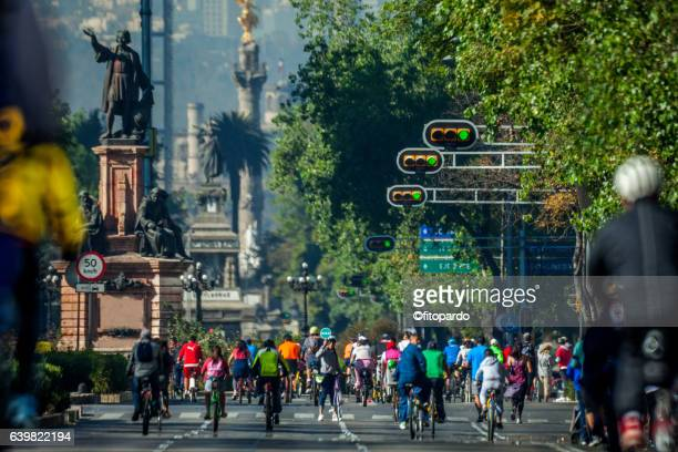 Reforma avenue Skyline in Mexico city and people riding bicycles