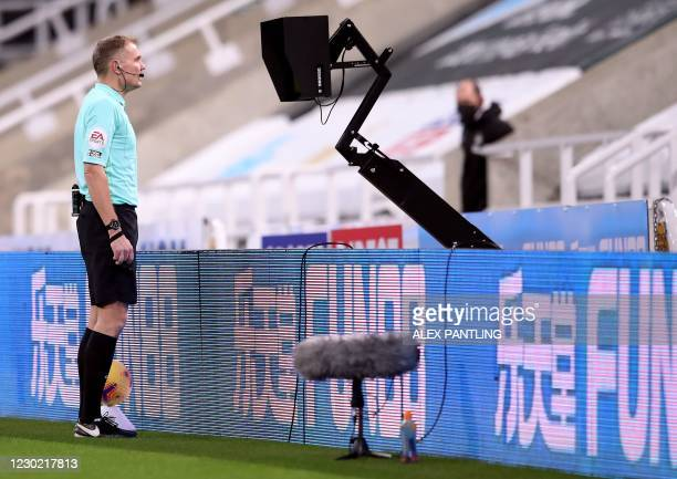 Refree Graham Scott reviews a penalty decision after Newcastle United's English striker Callum Wilson was fouled by Fulham's Danish defender Joachim...