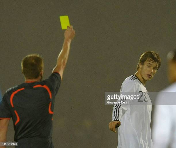 Refree Igor Ishchenko shows the yellow card to Holger Badstuber of Germany during the UEFA Under 21 Championship match between San Marino and Germany...