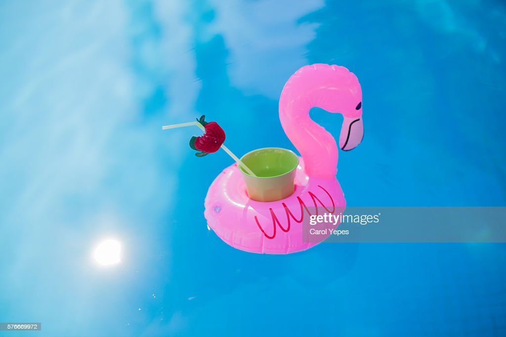 Refreshing beverage in a pink flamingo floating cup holder in the pool : Stock Photo