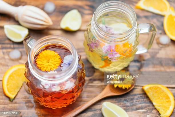 refreshing mineral water with edible flowers, viola wittrockiana, dianthus caryophyllus, calendula officinalis, lemon and orange - pot marigold stock pictures, royalty-free photos & images