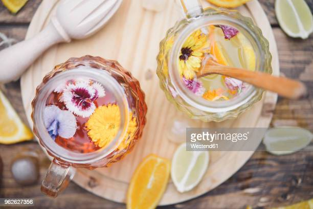 refreshing mineral water with edible flowers, viola wittrockiana, dianthus caryophyllus, calendula officinalis, lemon and orange - infused water stock pictures, royalty-free photos & images