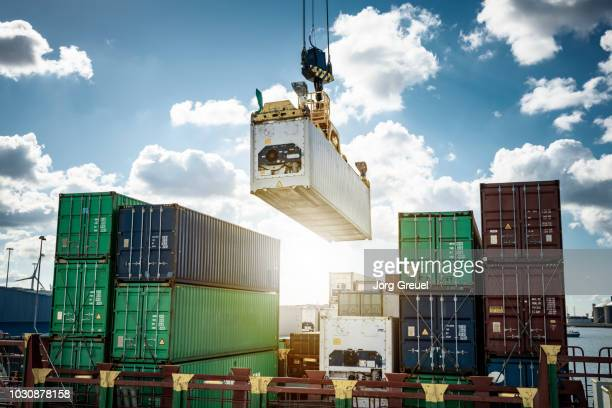 refrigerated container being loaded on a container ship - porto marittimo foto e immagini stock