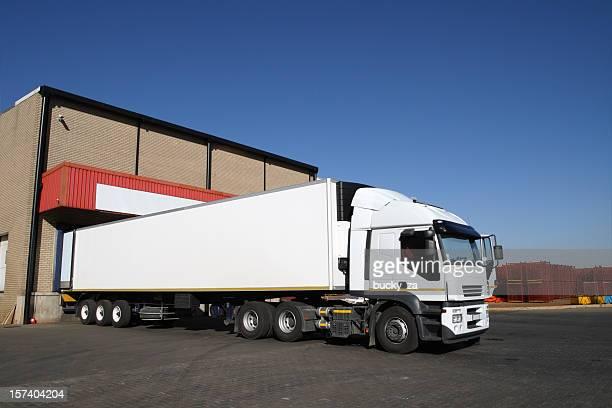 Refrigerated semi truck at a cold storage warehouse loading bay.