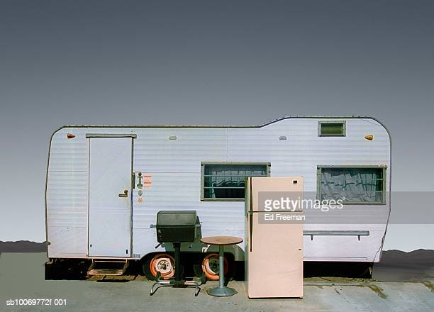 Refrigerator and table by mobile home in trailer park, close-up
