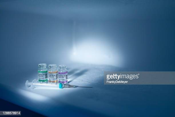 refrigerator compartment storing covid-19 vaccine vials at low temperature with syringe. labeled sars-cov-2 against coronavirus - storage compartment stock pictures, royalty-free photos & images
