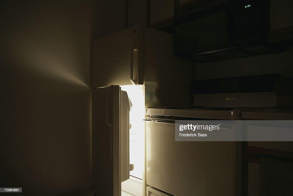 Refrigerator door open at night : Stock Photo