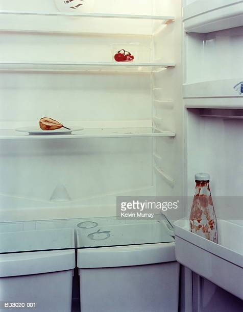 refrigerator with empty ketchup bottle and old pear, close-up - empty fridge stock pictures, royalty-free photos & images