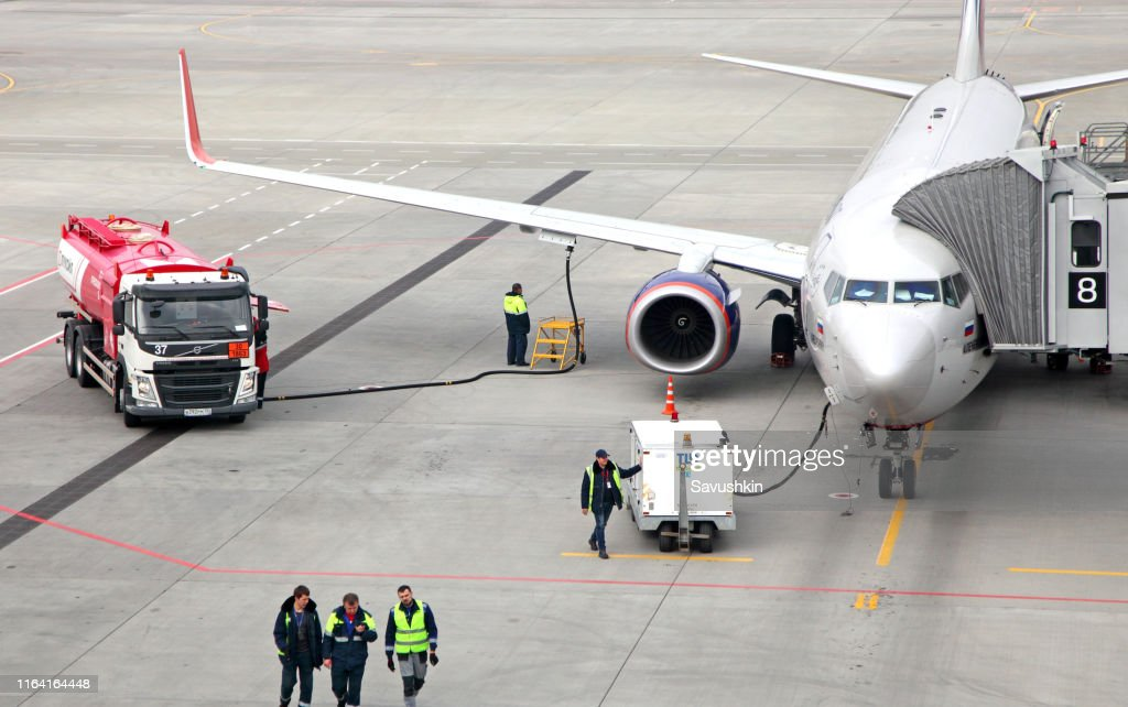 Refueling aircraft from tanker vehicle : Stock Photo