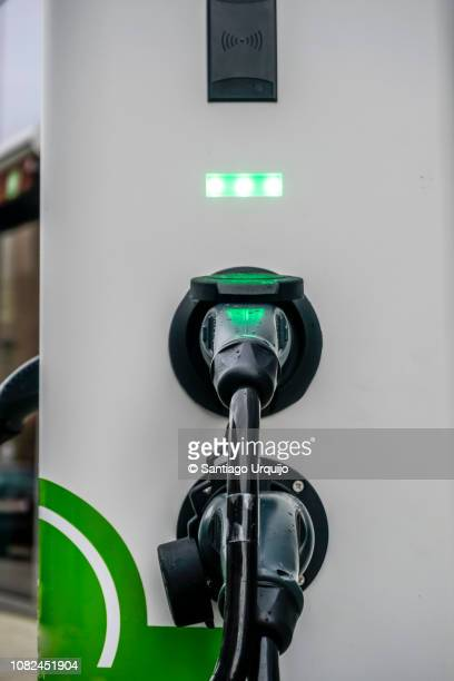 refueling an electric hybrid car - electric vehicle charging station stock pictures, royalty-free photos & images