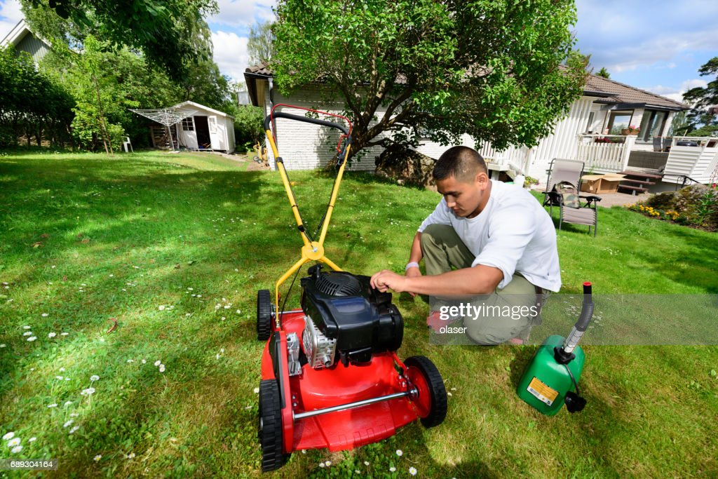 Refueling, maintenance / mowing the lawn in nice green garden. : Stock Photo