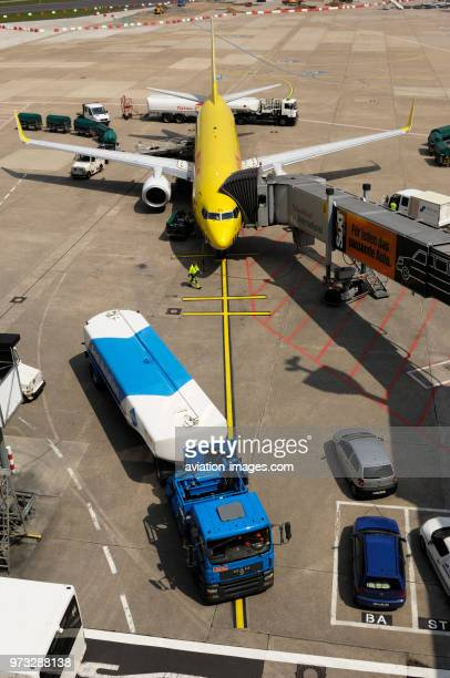 refuelling bowsers tractor with baggage trolleys and TUIfly Boeing 737800 parked with jetway attached