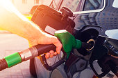 Refuelling the car at a gas station fuel pump. Man driver hand refilling and pumping gasoline oil the car with fuel at he refuel station. Car refuelling on petrol station. Fuel pump at station