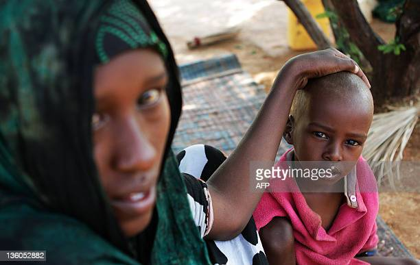 Refugee Abshiro Isakbul sits by her sick son at the Transit Centre in Dolo Ado Ethiopia on December 15 2011 Over 300000 refugees have fled severe...