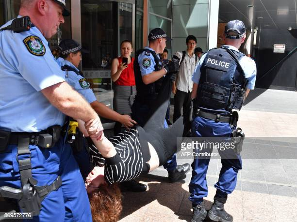 A refugee advocate is taken away after arrested by police officers following a crackdown on demostrators blocking the main entrance of the...