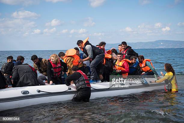 refugee boat arriving on lesbos greece - human trafficking stock photos and pictures