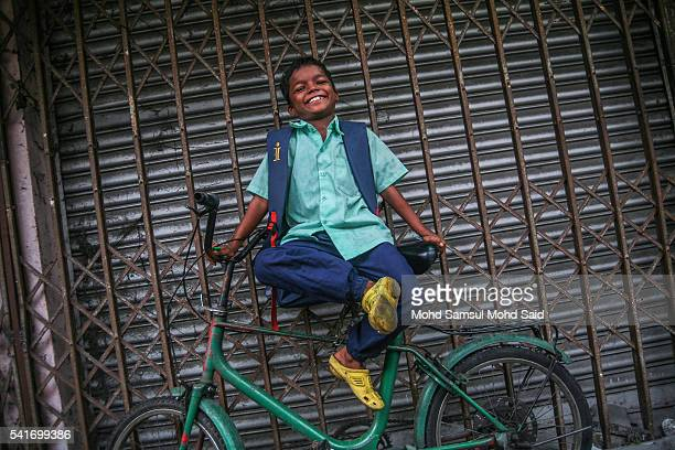 A refugee boy from the Rohingya ethnic minority smiles as he waits on a bicycle before going to school on June 20 2016 in Klang Malaysia According to...