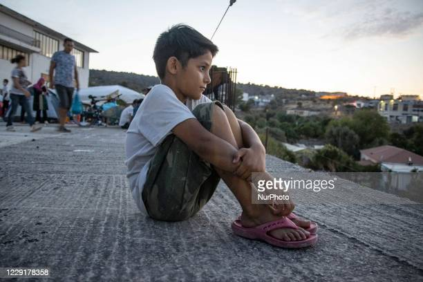 Refugee boy is staring from the roof of the building the new Karatepe refugee camp. Portraits of young children refugees, minors boys and girls,...