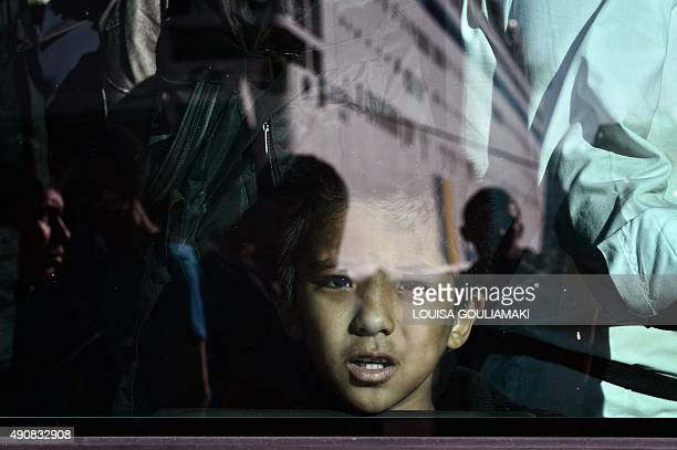 A refugee boy looks out from a bus window after disembarking in the port of Piraeus from the Eleftherios Venizelos goverment chartered ferry on...