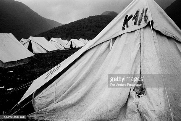 Refugee boy looks out of his family tent on April 21, 1999 in a refugee camp in Cegrane, Macedonia. Tens of thousands of people fled from Kosovo from...