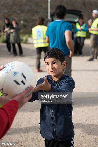 Refugee boy receives football to play with from volunteer