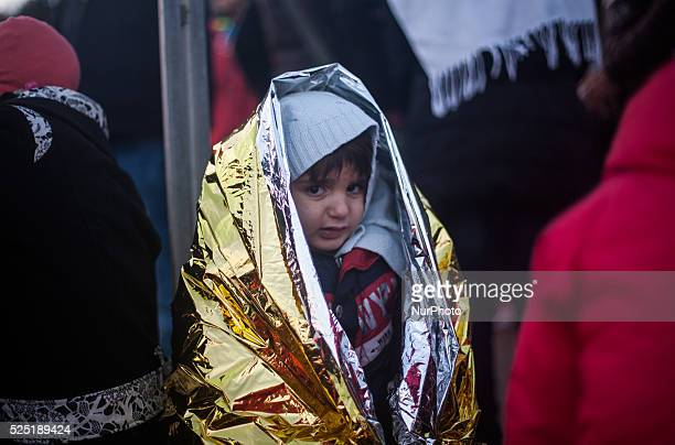 A refugee boy warms up in a thermal blanket after the arrival with his family by boat on Lesbos / Skala Skamineas January 14 2016