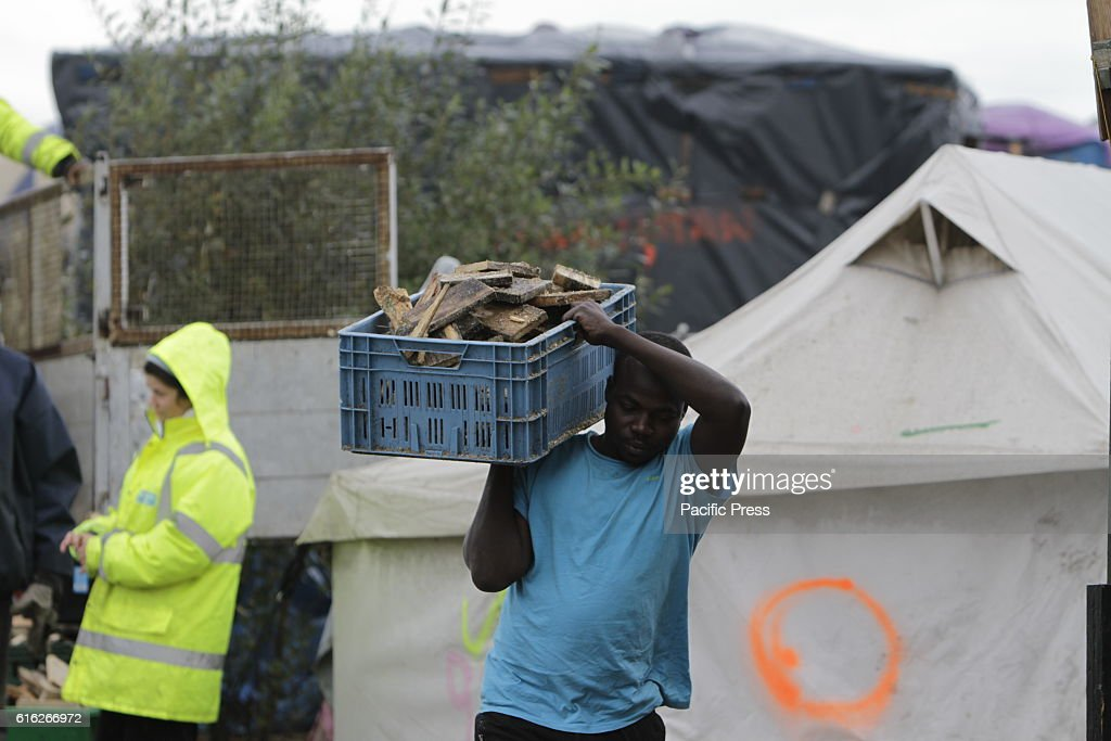 A refugee carries a box with wood through the jungle. Day to day life in the Jungle continues with just days to go to the eviction of the camp by the French state. However more and more people are leaving the camp and the number of empty tents and huts increases.
