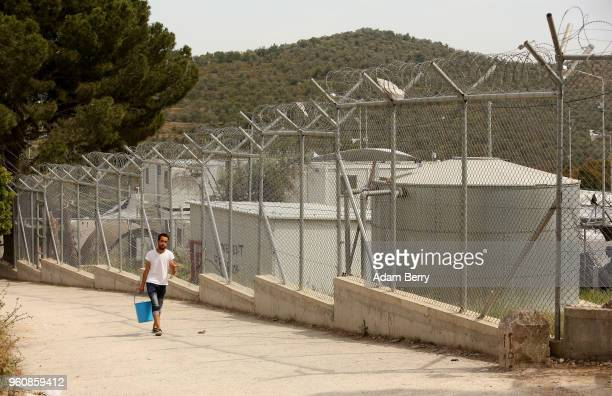 A refugee carries a bucket to fill with water at the Moria refugee camp on May 20 2018 in Mytilene Greece Despite being built to hold only 2500...