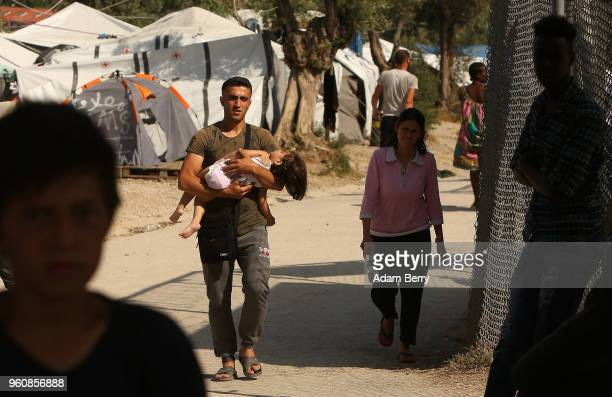 A refugee carries a child through the Moria refugee camp on May 20 2018 in Mytilene Greece Despite being built to hold only 2500 people the camp on...