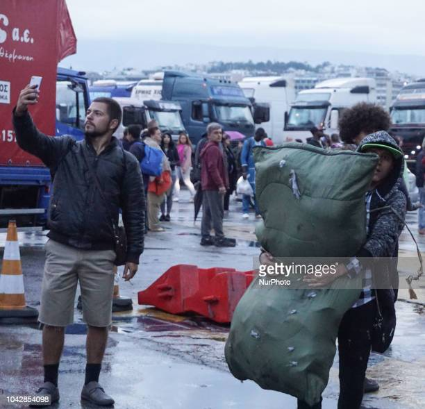 A refugee carry his belonging items after they disembark from a ferry at the Port of Piraeus 29 September 2018 Thousand migrants and refugees are...