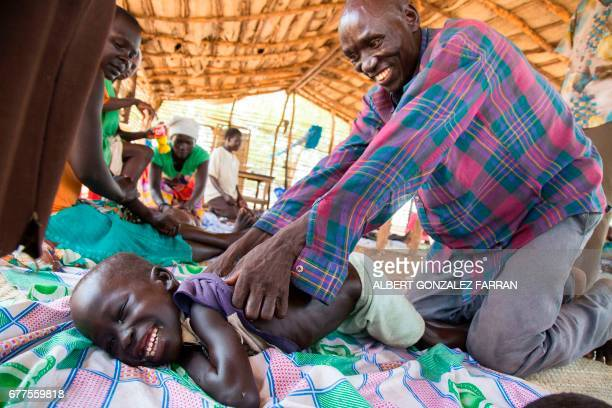Refugee child from Sudan with disabilities is massaged at Doro refugee camp, in Maban, near Bunj, South Sudan, on May 3, 2017. Massagers from the...